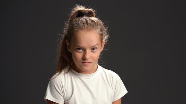 Злобная маленькая девочка с волосами в виде конского хвоста смотрит вперед в белой футболке и черных штанах, изолированных на черной стене