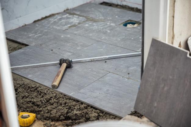 Молоток и инструменты на гранитной плитке во время укладки пола