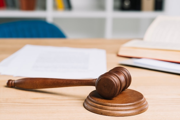 Mallet on gavel over wooden table in courtroom