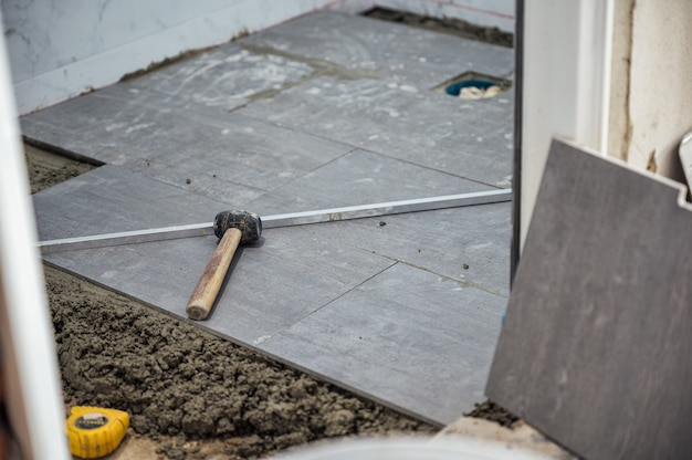 Mallet and tools on granite tile during laying floor