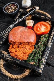 마요르칸 소브라사다(mallorcan sobrassada)는 나무 쟁반에 돼지고기 소시지를 숙성시켰다. 검은 나무 배경. 평면도.