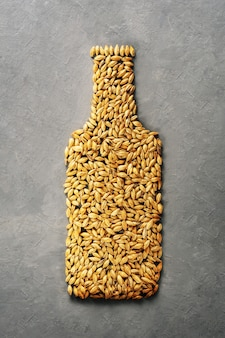 Malt grains are laid out as a beer bottle on a grey concrete background.