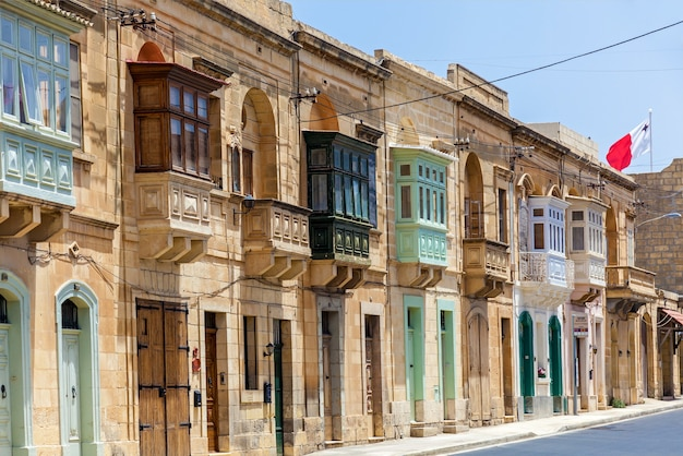 Malta valletta june 16, 2019: architecture of malta, the facade of the house with colorful wooden windows and a balcony on the island of malta
