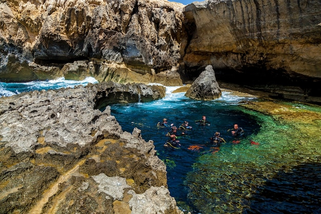 Malta valletta june 16, 2019: a beautiful canyon with pure bly water on a sunny day. a group of divers prepares to submerge under water.