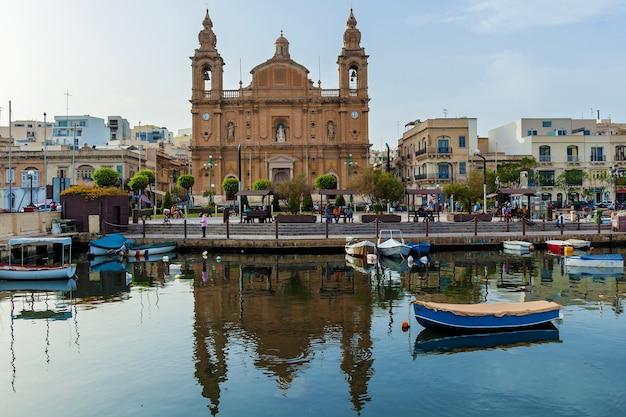 Malta valletta june 16, 2019: beautiful view of the catholic baroque church on the background of blue sky. amazing cityscape with old houses and traditional luzzus in the harbor.