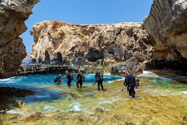 Malta valletta june 16, 2019: a lot of scuba divers in the equipment are entering the blue pure water of a small canyon on a sunny day. the canyon is surrounded by big stones.