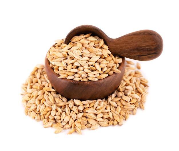 Зерна солодового ячменя в деревянной миске и ложке, изолированные на белом. семя ячменя заделывают.