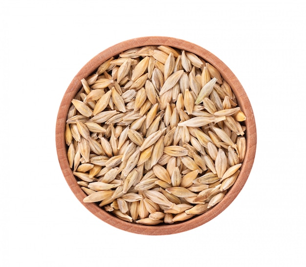 Malted barley grains in the wooden bowl, isolated. barley seed close up. top view. macro.