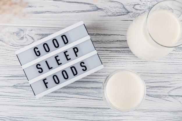良い睡眠食品の碑文の横にある瓶とガラスでぐっすり眠るための麦芽の夜のミルク