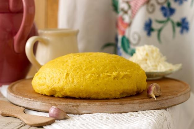 Mamaliaga or polenta, a traditional dish of moldovan, romanian, hungarian and ukrainian cuisine. porridge from corn flour. served with brynza, sour cream and garlic sauce.