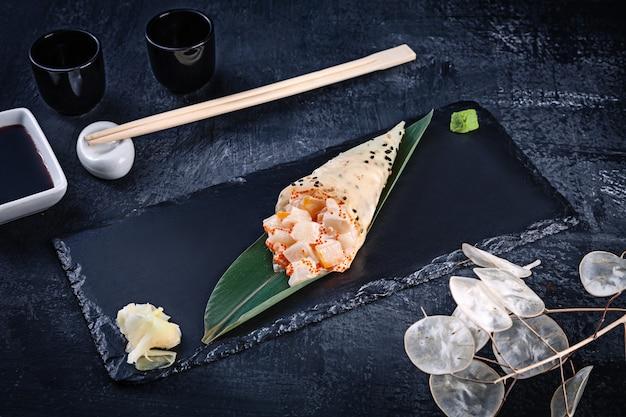 Крупным планом вкусные суши ролл руки в mamenori с морским гребешком и икрой тобико, подается на темной каменной плите с соевым соусом и имбирем. копировать пространство темаки, японская кухня. здоровая пища