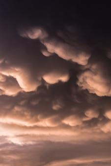 暖かいトーンで空を覆うマンモスの雲