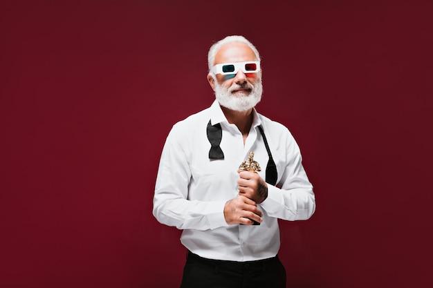 L'uomo con gli occhiali 3d tiene in mano la statuetta dell'oscar
