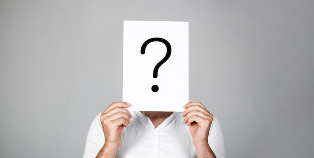 Возьми вопрос. сомнительный мужчина, держащий вопросительный знак. проблемы и решения. вопросительный знак, символ. задумчивый самец. получение ответов. портрет мужчины, заглядывая за символ допроса. мужчина изолирован