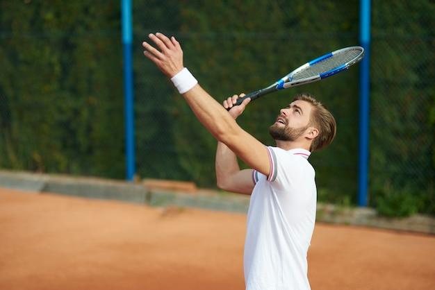 Человек собирается подавать теннисный мяч