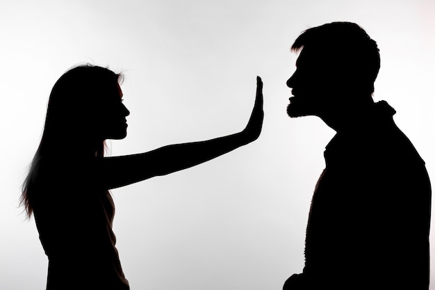 男性虐待女性、白い背景の上のシルエット。