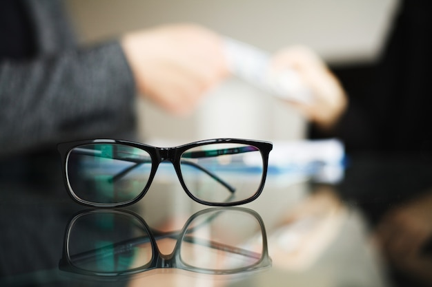 Man accepting money and glasses over the glass table