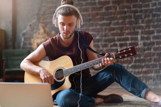 ラップトップとヘッドフォンで歌う歌のオンライン音楽レッスンを演奏する男のアコースティックギターの座っている床。楽器のビデオ通話を練習している白人の若いギタープレーヤーがガールフレンドのためにセレナーデを呼び出す