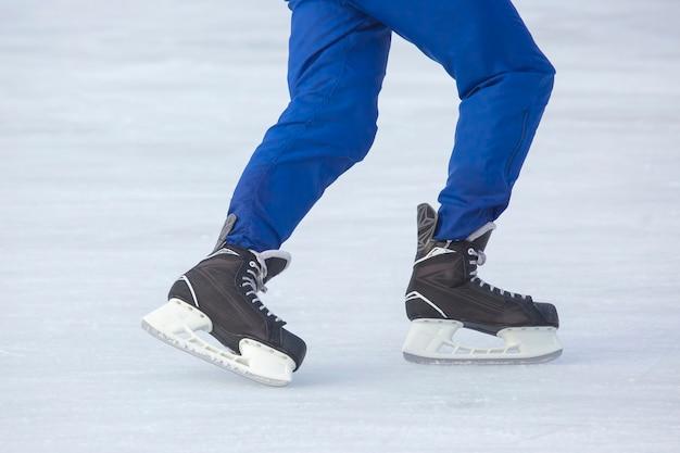 남자는 아이스 링크에서 적극적으로 스케이트를 타고 있습니다. 취미와 스포츠. 휴가 및 겨울 활동.