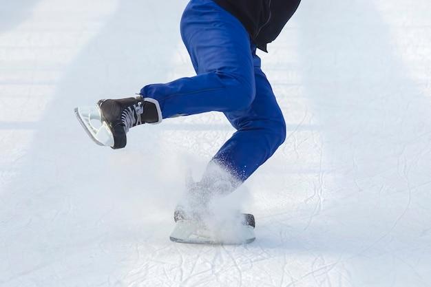 남자는 아이스 링크에서 적극적으로 스케이트를 타고 있습니다.
