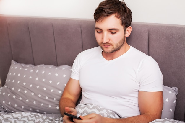 Man addicted to his mobile phone in bed