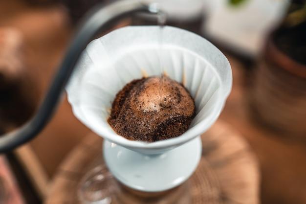 유리 항아리 위의 커피 드리퍼에 뜨거운 물을 추가하는 남자.