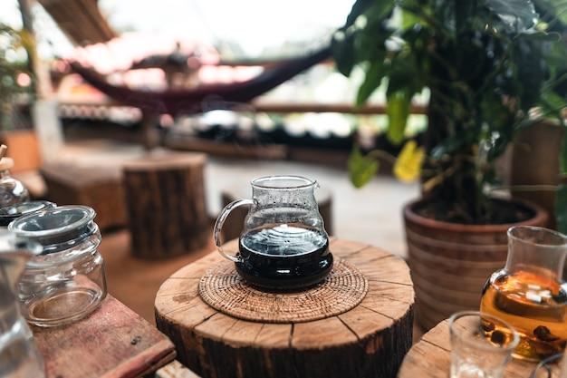 ガラスの瓶の上のコーヒードリッパーにお湯を追加する男。