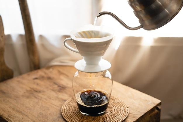 Человек добавляет горячую воду в капельницу для кофе над стеклянной банкой.