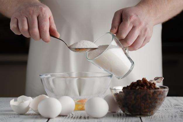 Man adding sugar to eggs in a bowl