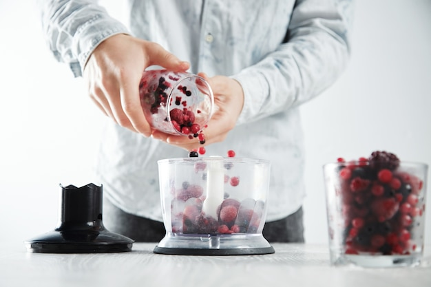 Man adds frozen berriess to focused blender pot with before making make tasty smoothie drink to refresh in summer time. unfocused glass with frozen berries in front near