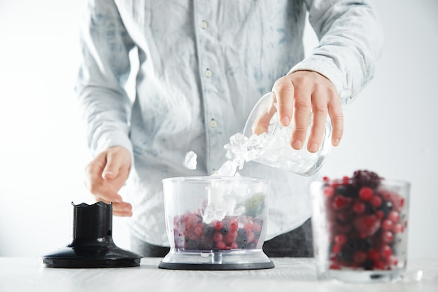 남자는 냉동 딸기와 함께 블렌더 냄비에 얼음 조각을 추가합니다