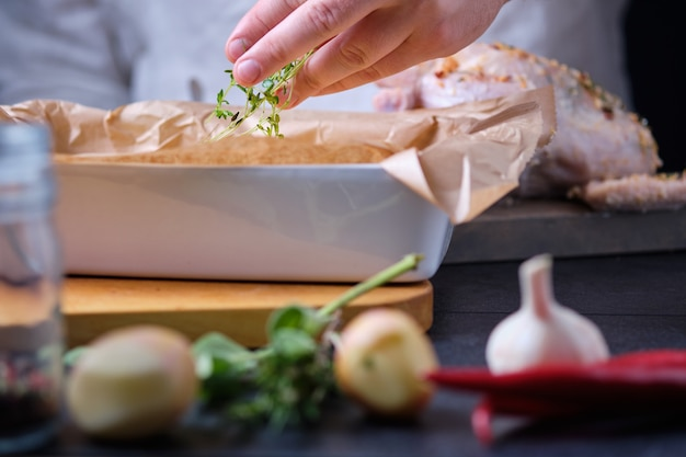 남자는 새 감자에 백리향을 추가합니다. 오븐에서 향신료와 레몬으로 닭고기를 요리하는 과정.