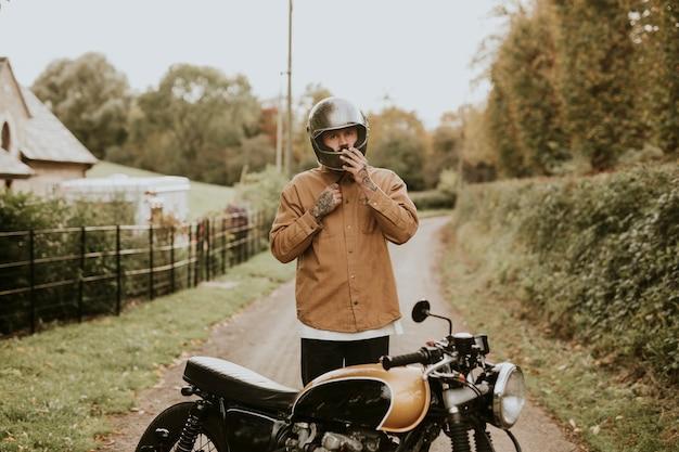 田舎に駐車した自転車でヘルメットストラップを調整する男