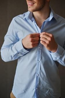 Man adjusting his shirt buttons.