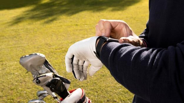 남자 골프 필드에 그의 smartwatch 조정