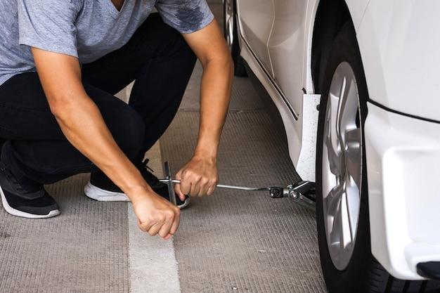 자동차 타이어 또는 유지 보수를 위해 높이를 높이기 위해 자동차의 잭 나사를 조정하는 남자