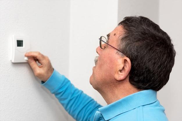 남자 집에서 온도 조절 장치, 얼굴에 초점을 조정합니다. 섭씨 온도 눈금.