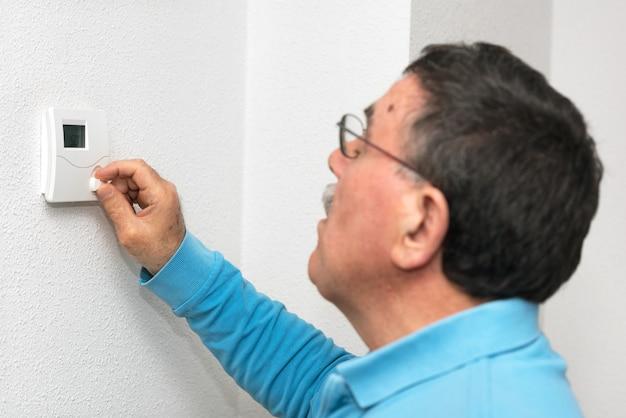 남자 집에서 온도 조절 장치를 조정, 온도 조절기에 초점. 섭씨 온도 눈금.