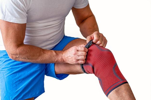 男性は膝関節の圧迫包帯を調整します。スポーツ傷害。