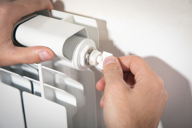 Мужчина регулирует воздушный клапан на радиаторе отопления.