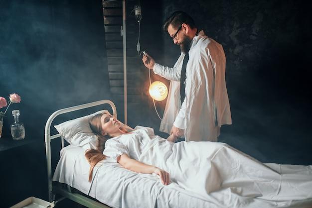 男は病院で病気の女性の点滴を調整します