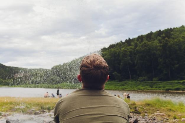 Человек любуясь видом на озеро и природу