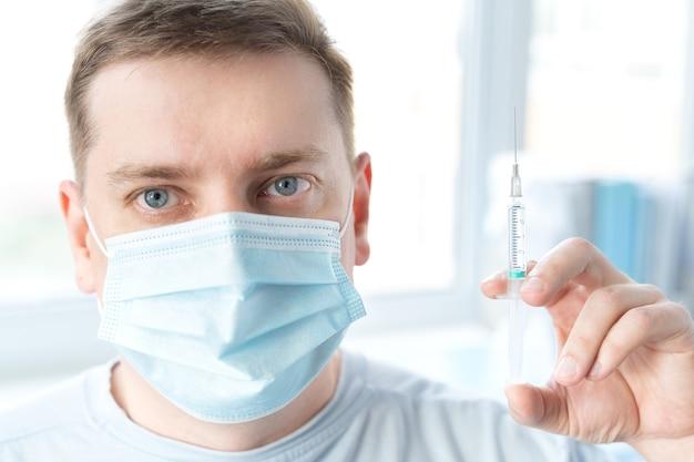 男性、診療所のフェイスマスクの大人が予防接種を受けています。 covid-19コロナウイルス、インフルエンザ、危険な感染症のワクチンを含む注射器。人間、子供のための臨床試験後の注射。薬。
