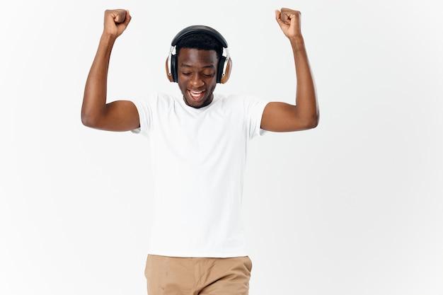 音楽の感情の明るい背景を聞いている男のアフリカの外観のヘッドフォン