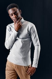 暗い背景をポーズする男のアフリカの外観モダンなスタイルの自信