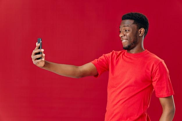電話を手に持つアフリカ人の姿 テクノロジーコミュニケーションの喜び