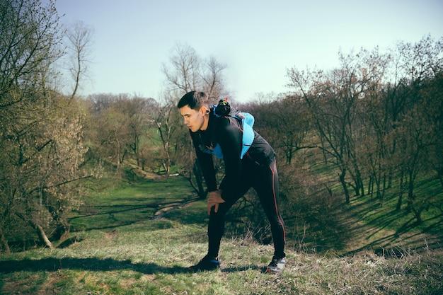 木々の空間に対して公園や森を走った後の男