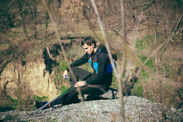 Uomo dopo aver corso in un parco o in una foresta contro gli alberi