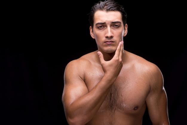 Man after taking shower on dark background
