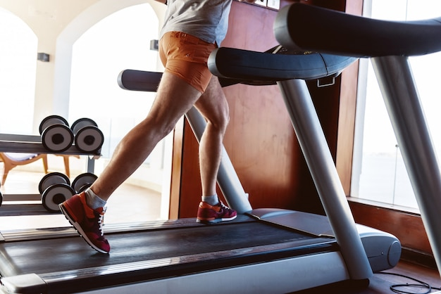 A man of age is engaged in running on a treadmill